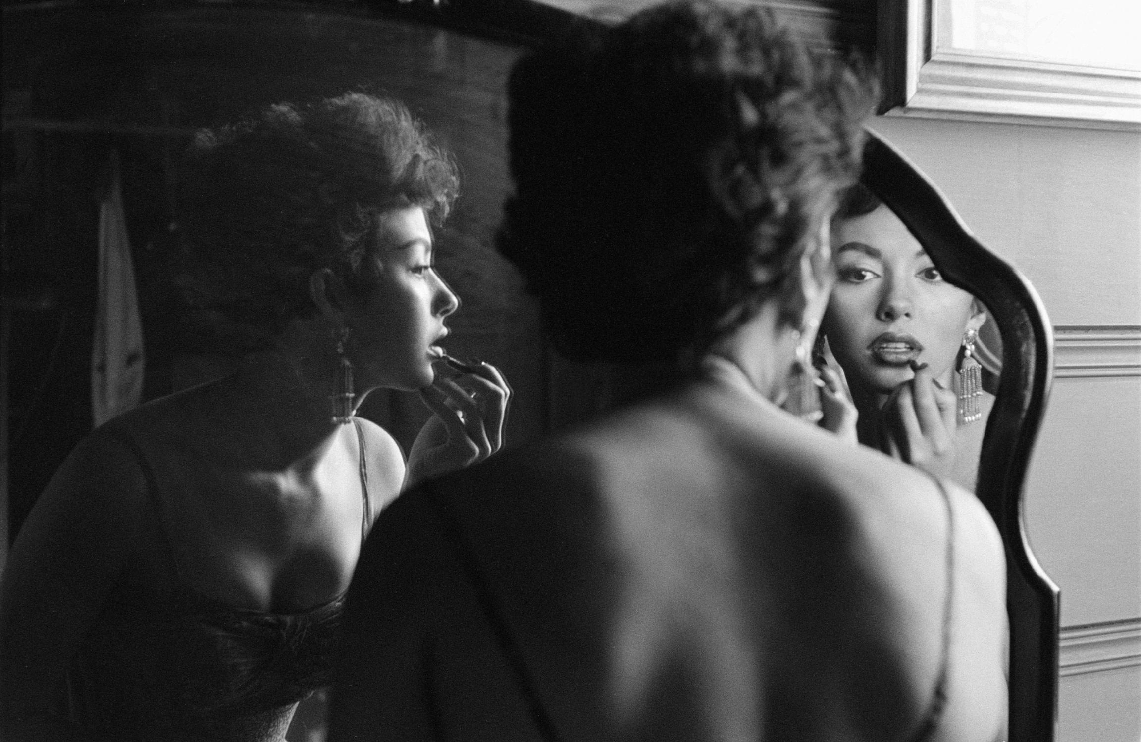 Rita Moreno Putting On Lipstick In Mirror, 1954