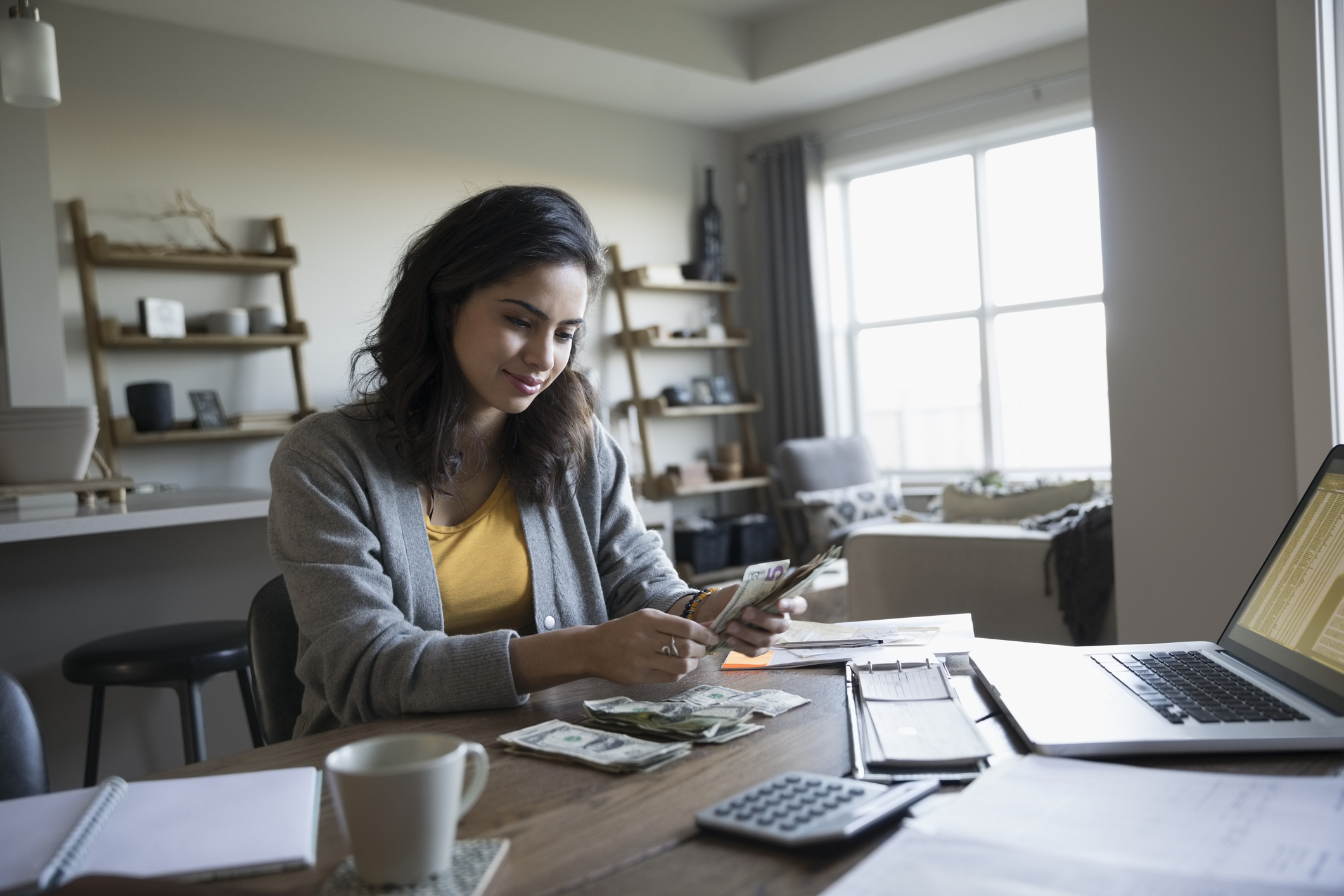Young woman counting cash managing personal finances in dining room