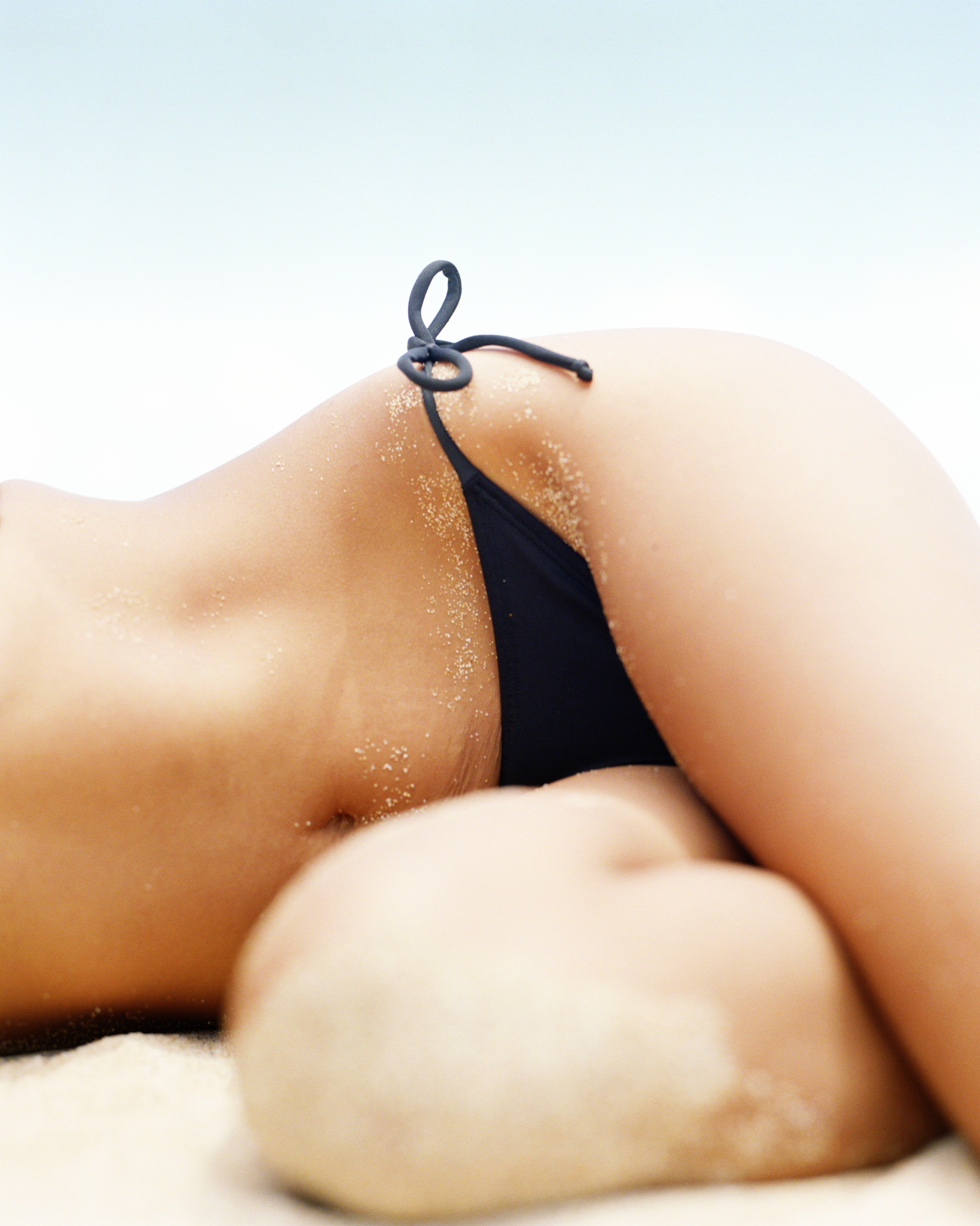Woman wearing black bikini , lying in sand on beach, mid section