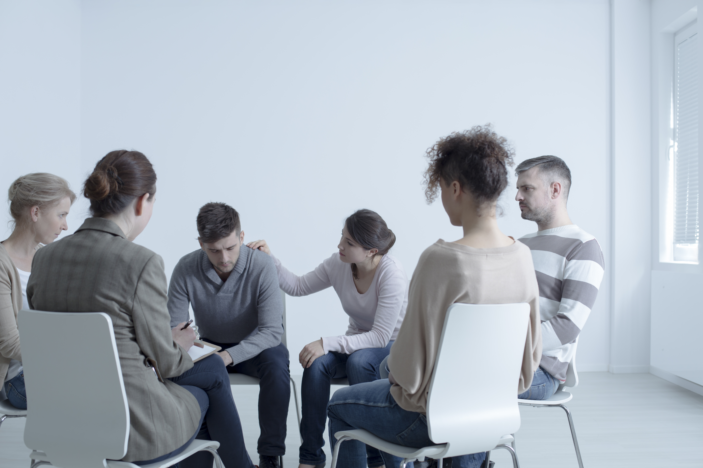 Psychotherapist comforting man