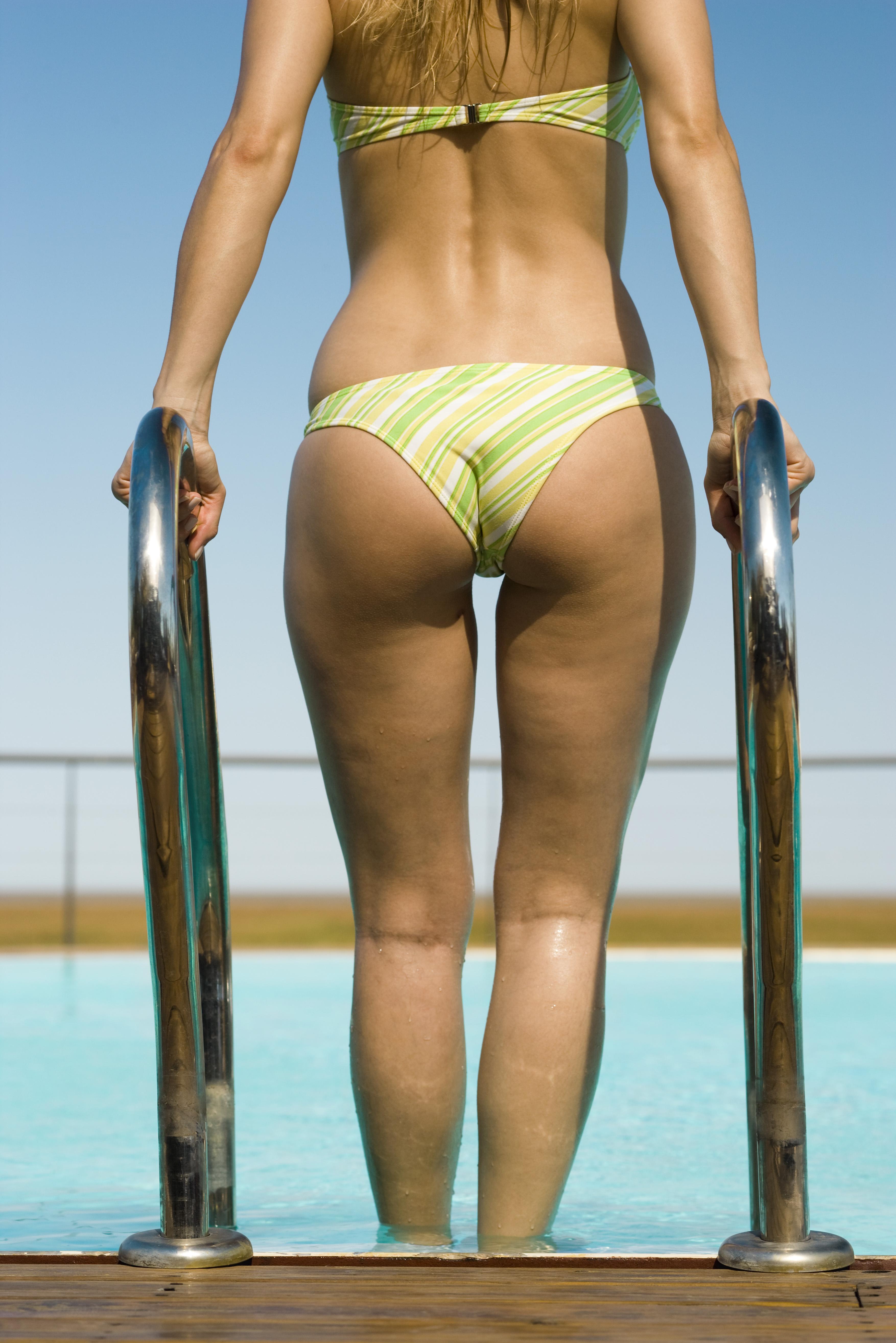 Woman entering swimming pool, rear view