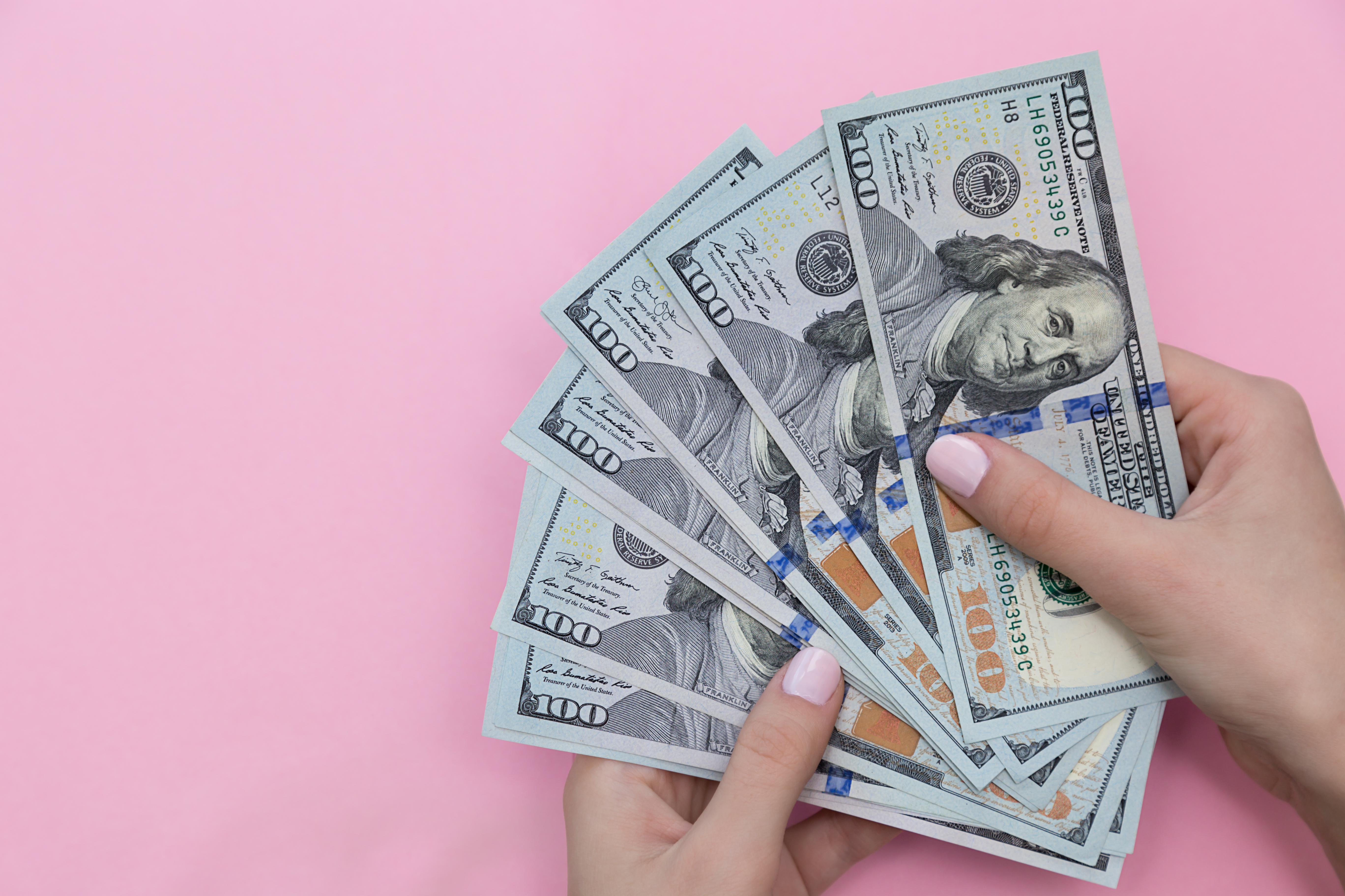 Cropped Hand Of Woman Holding Paper Currencies Against Pink Background