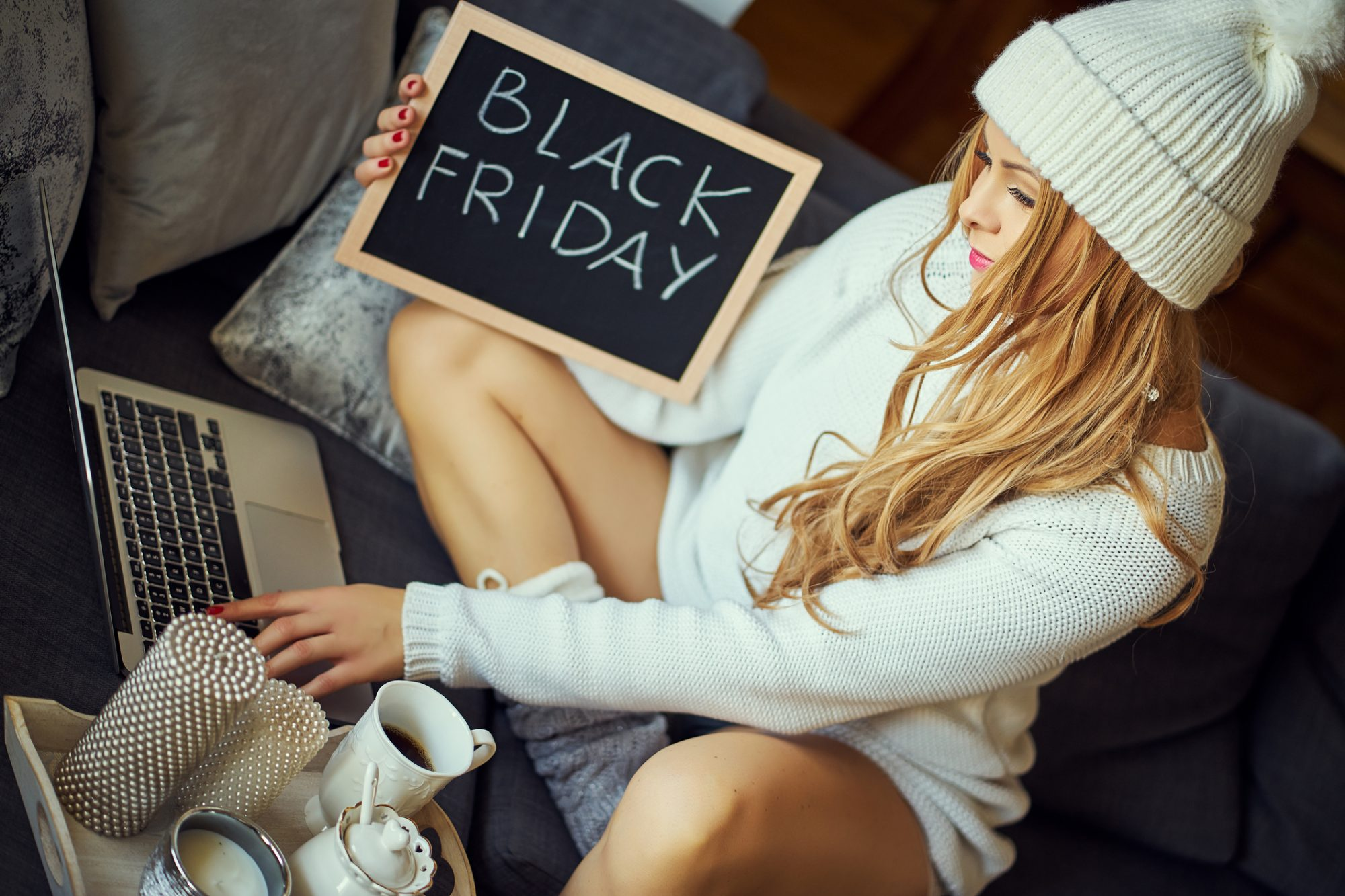 Woman With Black Friday Text Sitting On Sofa At Home