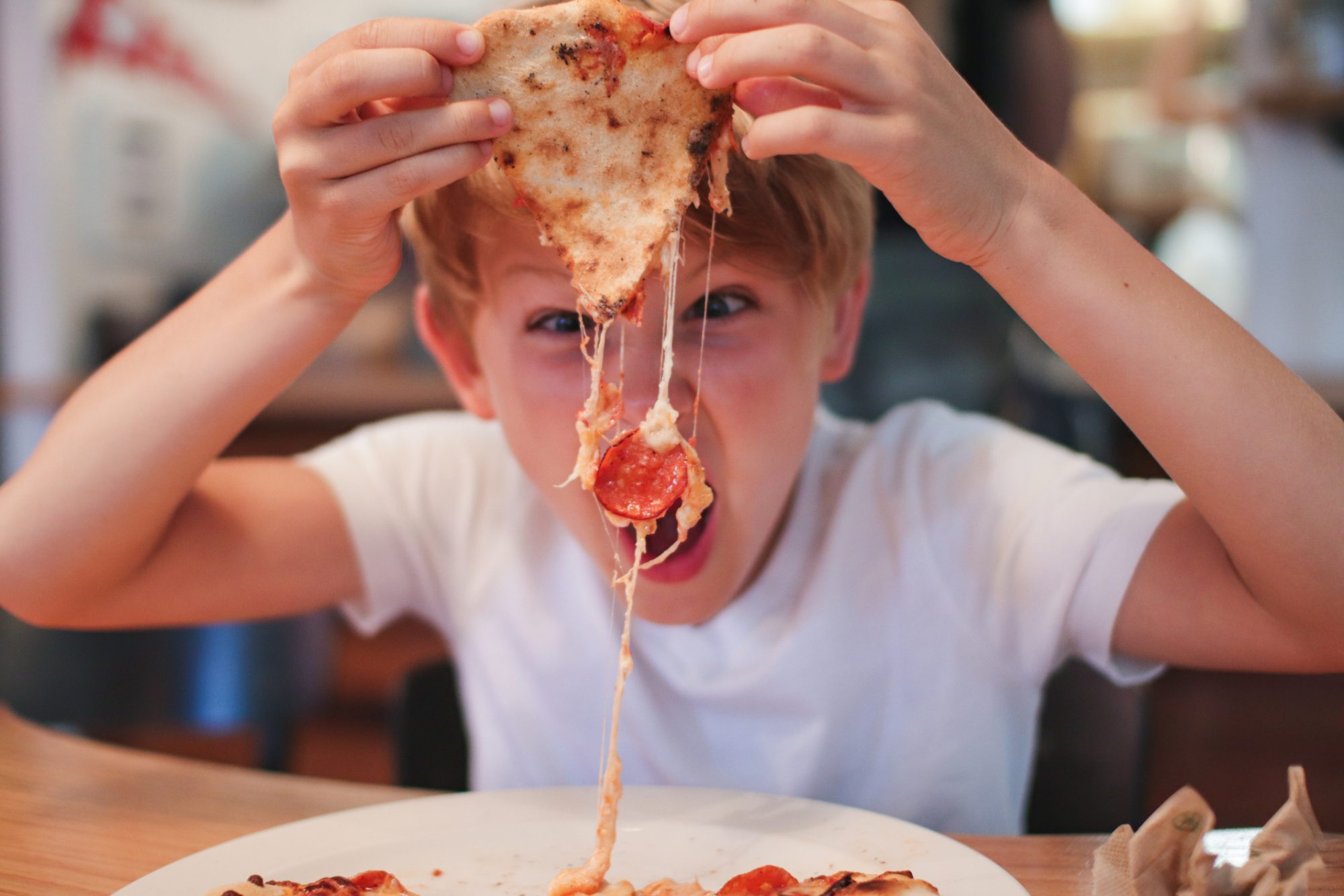 Portrait Of Boy Eating Pepperoni Pizza