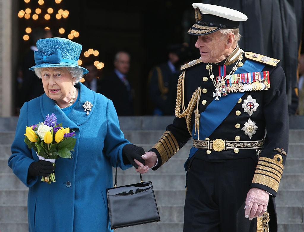 Reina Isabel principe Carlos de la mano