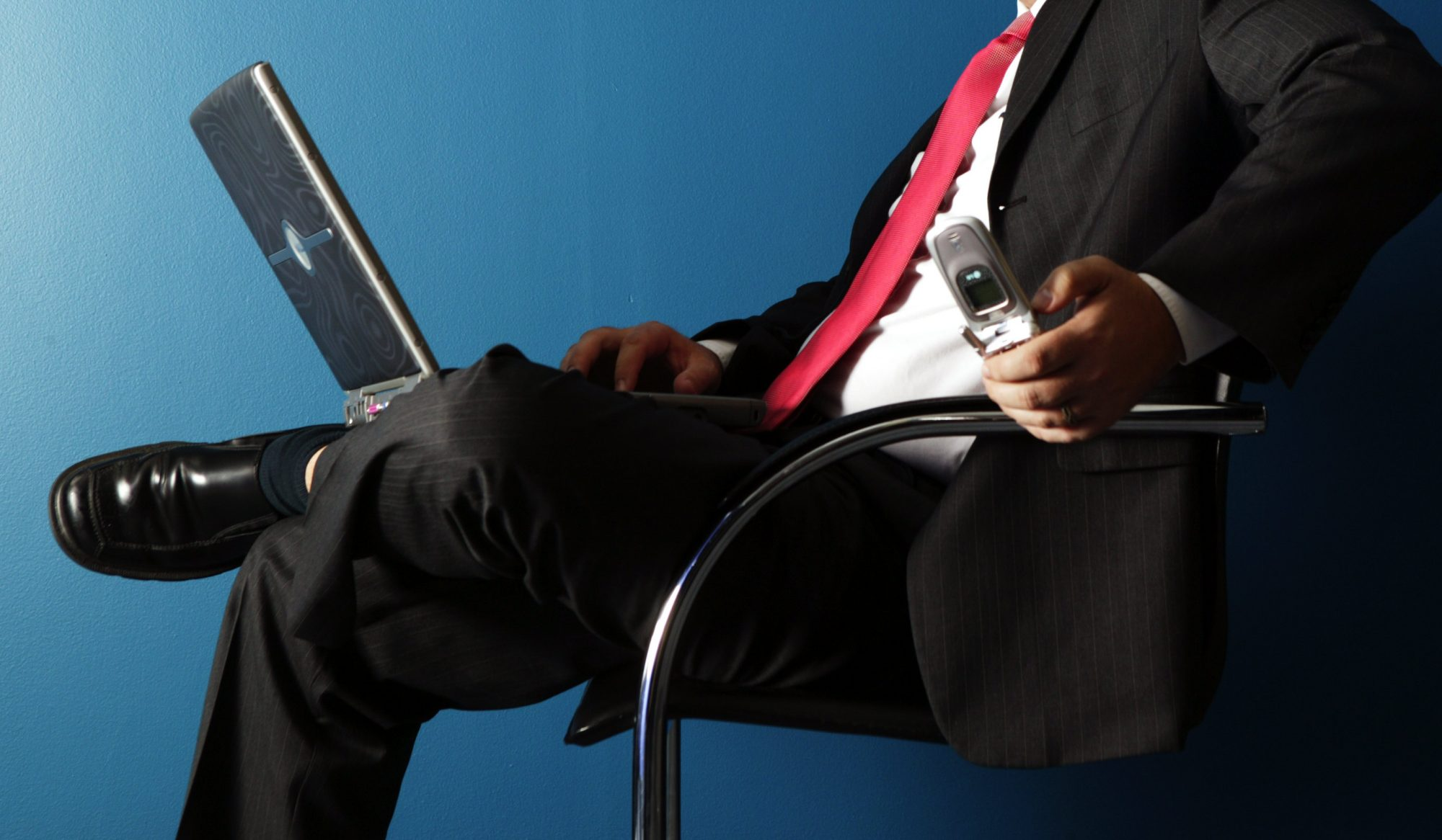 A seated businessman uses a laptop and mobile phone, 24 May 2005. AFR Picture