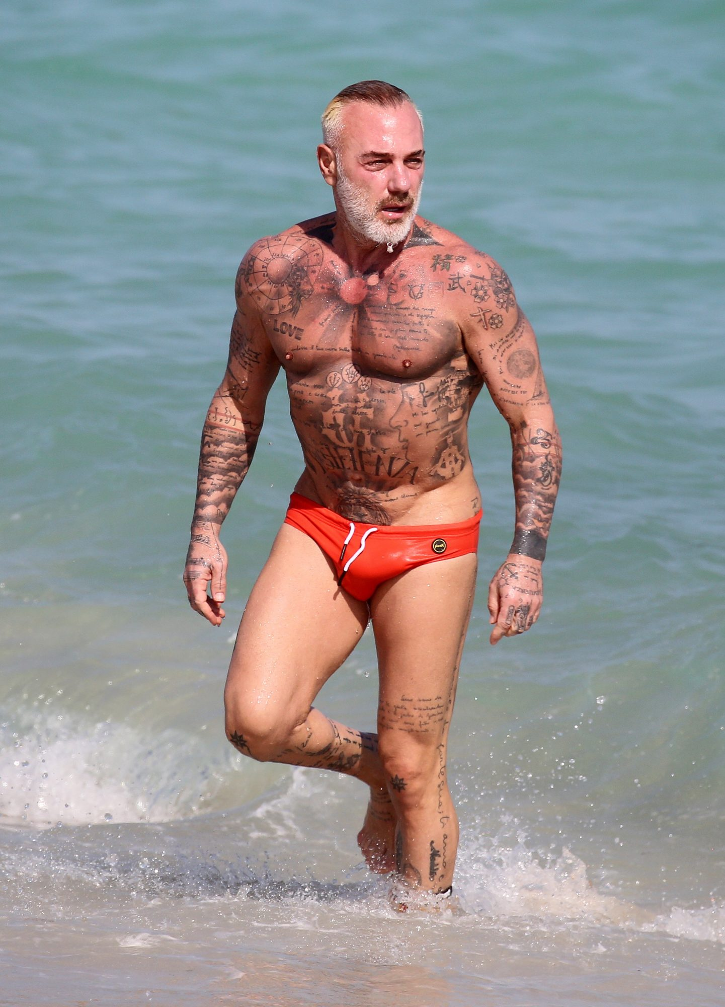 DJ Gianluca Vacchi shows off his tattoos in a tiny speedo on the beach in Miami