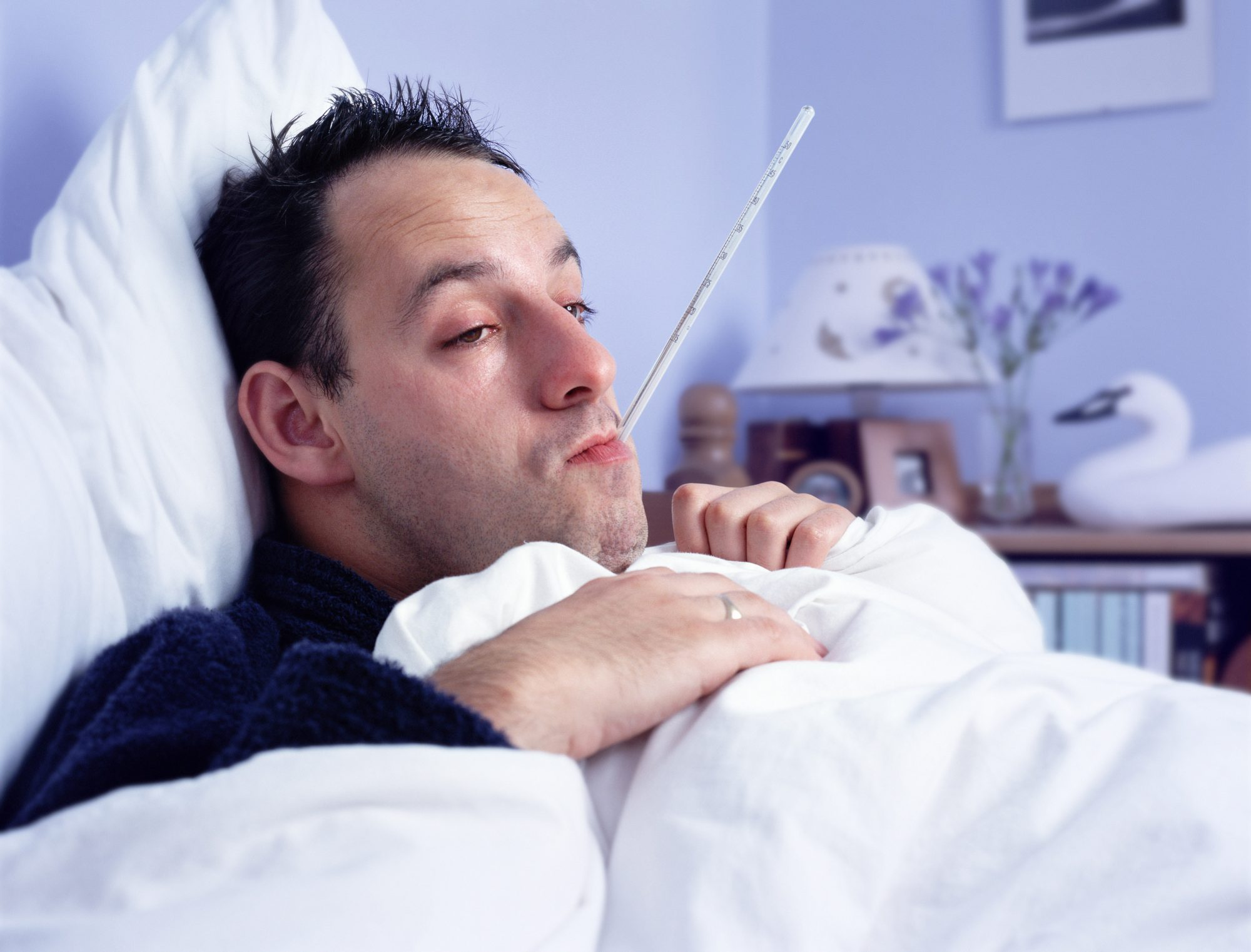 Man lying in bed, with thermometer in mouth, close-up (Enhancement)