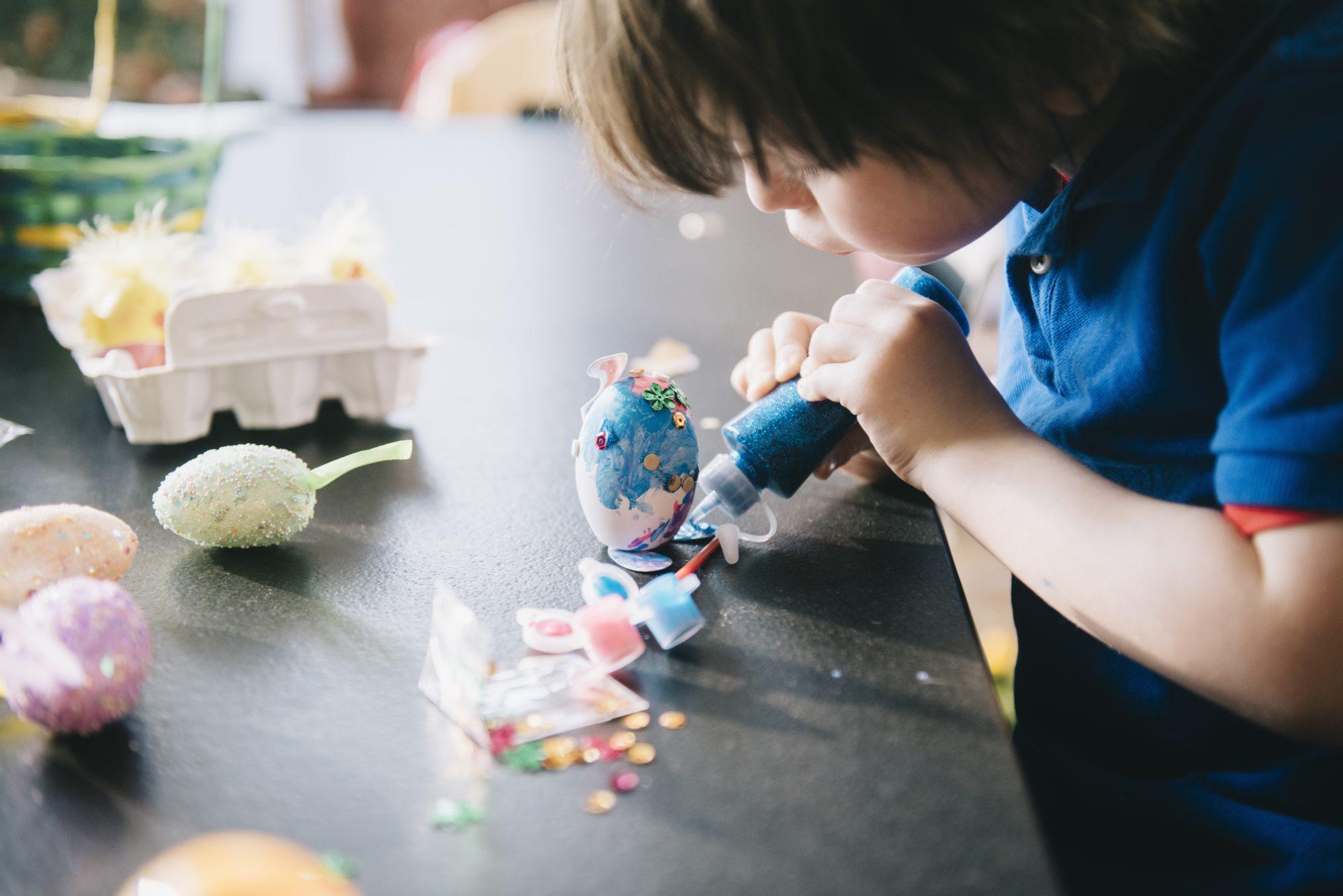 Niño decora huevos de Pascua