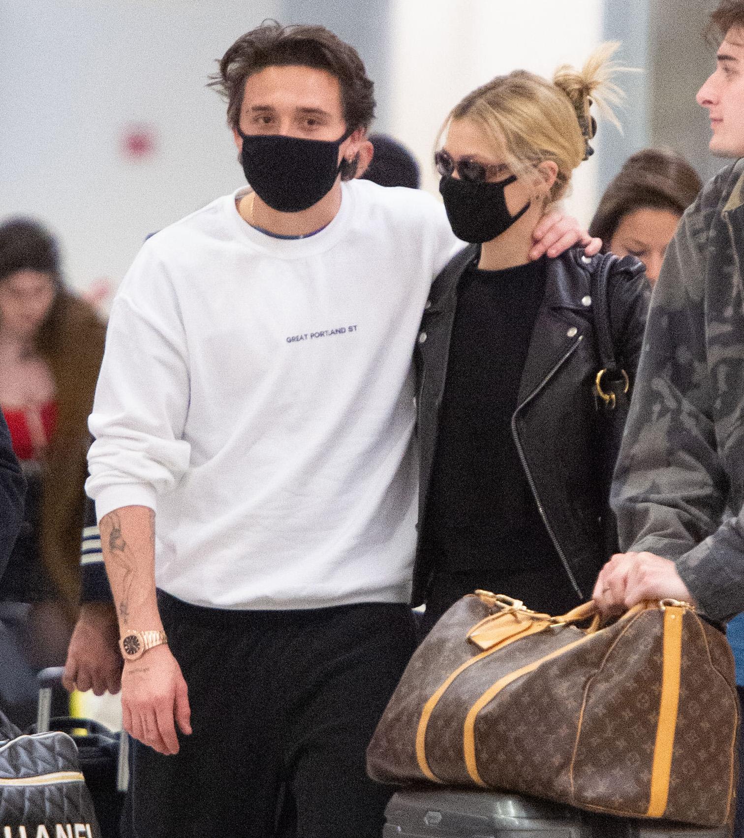 Brooklyn Beckham and girlfriend Nicola Peltz wear matching masks upon arrival at JFK Airport in New York City.