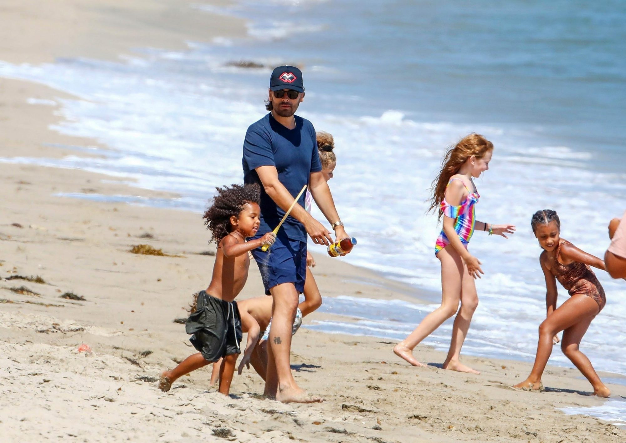 Malibu, CA - Scott Disick enjoys a day at the beach with his kids, Kim and Kanye's kids, and TikTok star Addison Rae in Malibu. Scott watches over the children as they play near the ocean as Kourtney Kardashian holds down the fort from the beach house balcony.