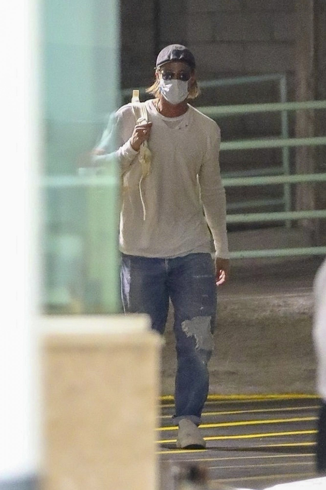 Brad Pitt keeps it safe wearing a mask as he arrives at a business building in L.A carrying a backpack