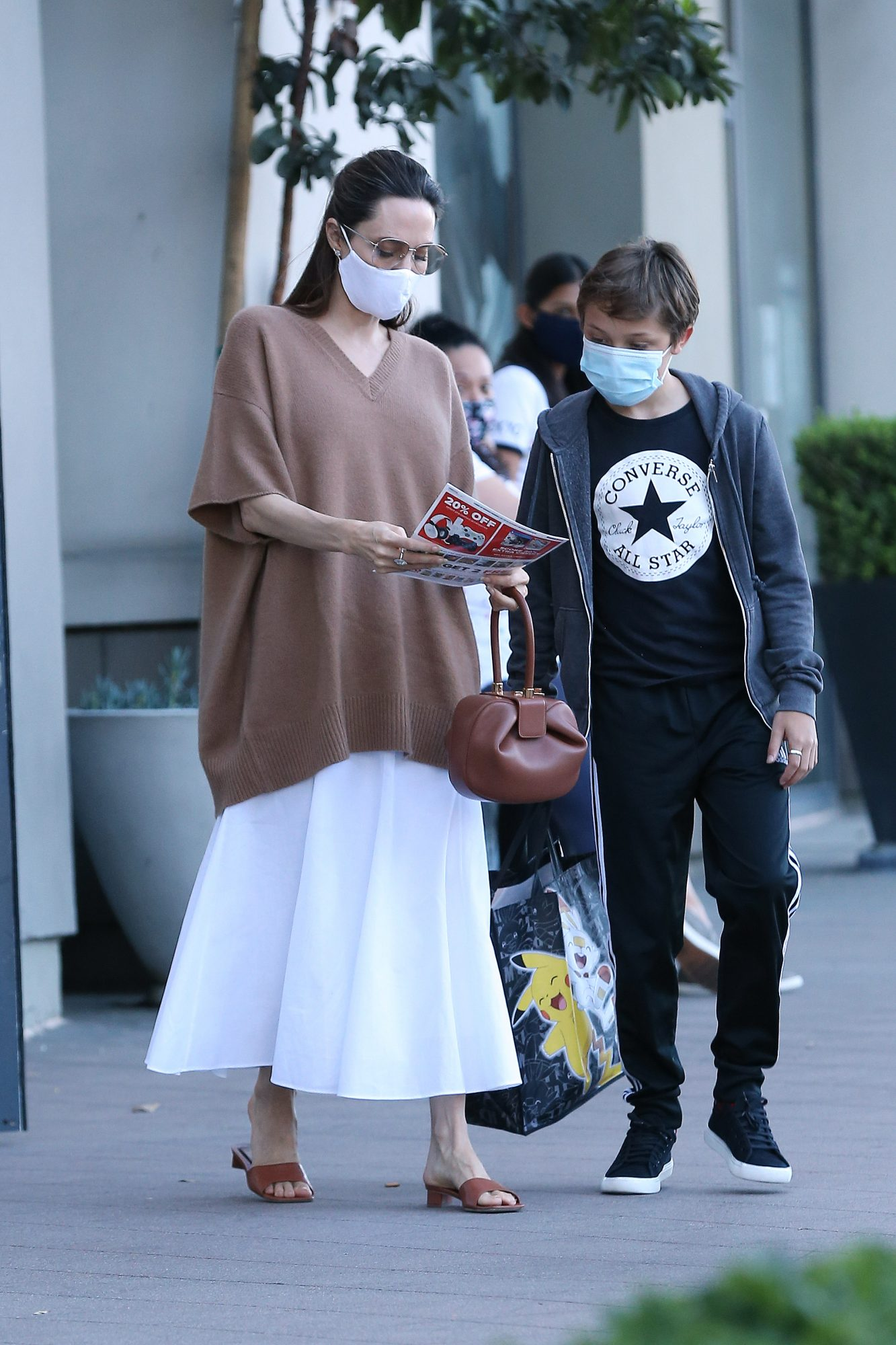 Angelina Jolie and and her son Knox hit up the video game store, GameStop in Los Angeles. Jolie carried the 'Nina Bag' by Gabriela Hearst; the bag is named for artist and activist Nina Simone. The 45 year old actress switched up from her normal all black outfits, wearing an oversized brown sweater, white skirt, and brown sandals.