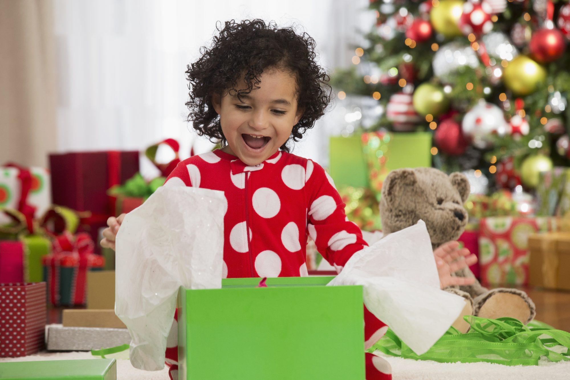 Niña latina pequeña sbriendo regalo Navidad
