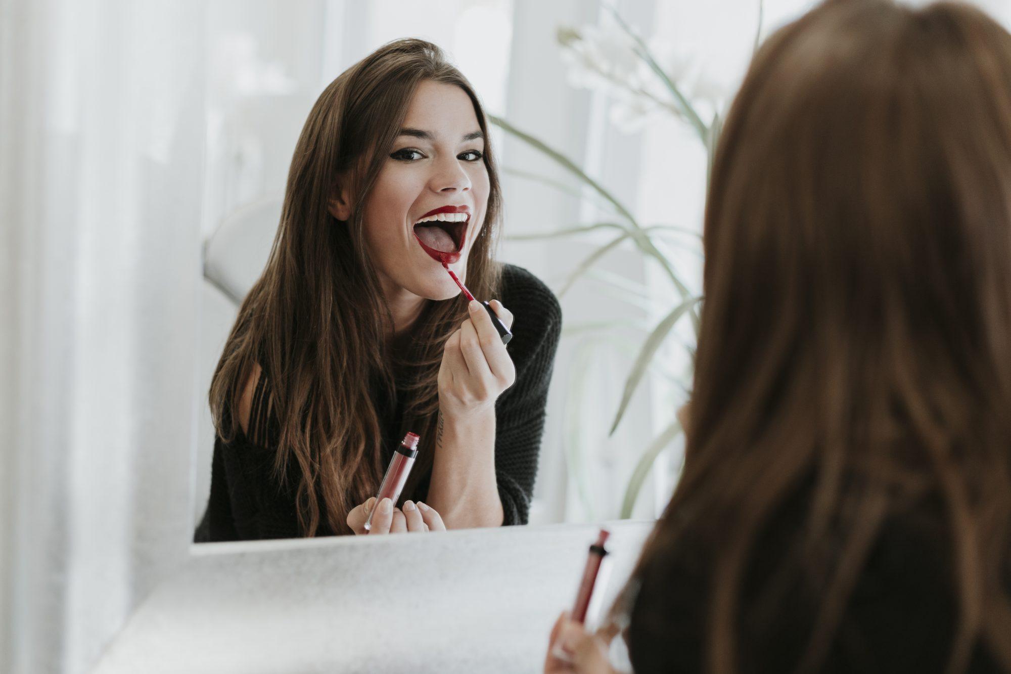 Mujer pintándose labios pintalabios espejo