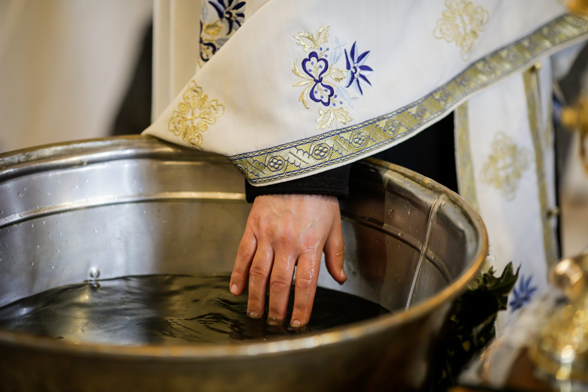 Orthodox priest testing the warmth of the water in the baptismal font