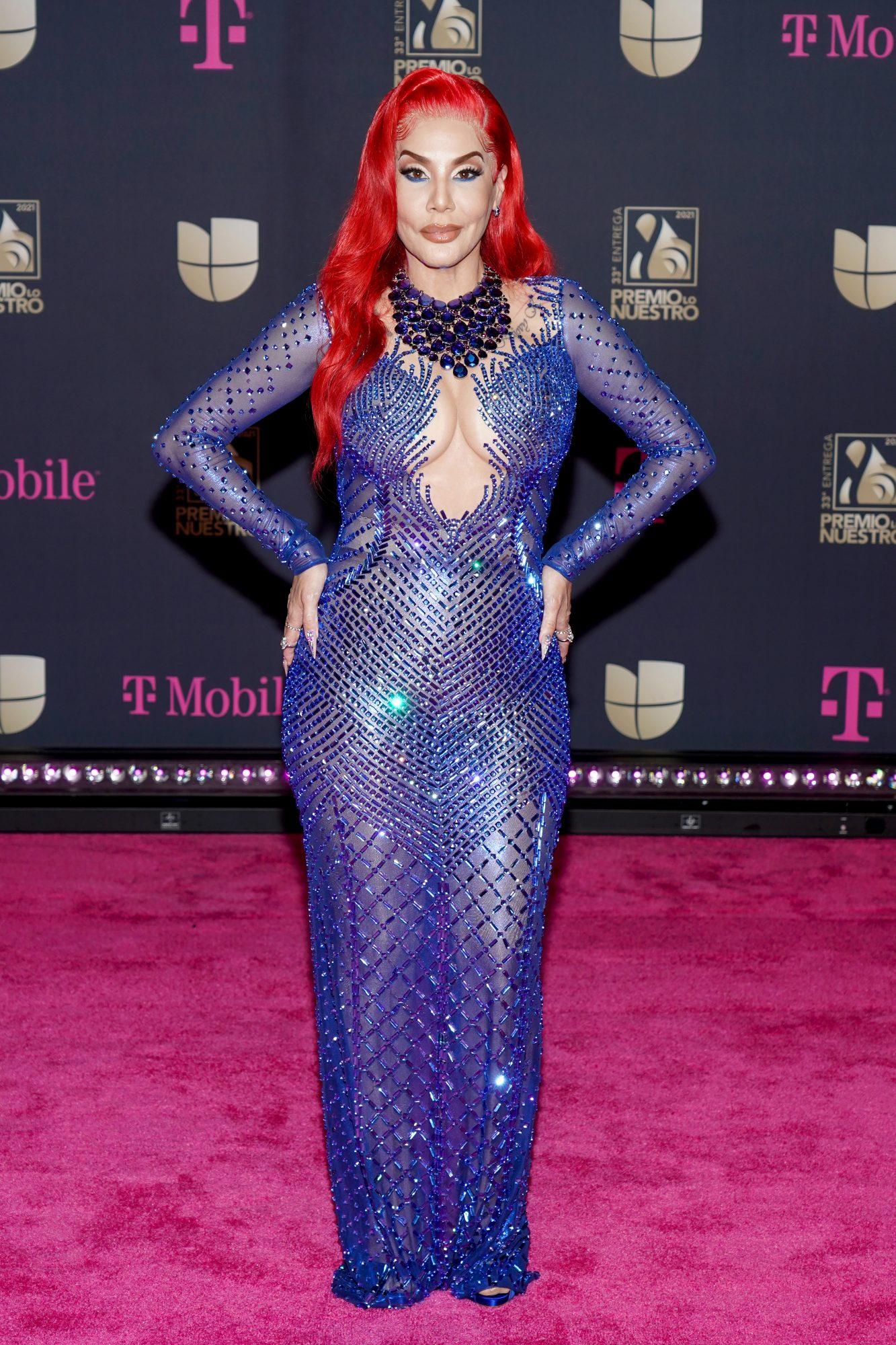 La reina del reguetón eligió este sensual diseño azul marino con revelador escote, transparencias y pedrería. ¿Qué tal su pelo rojo?