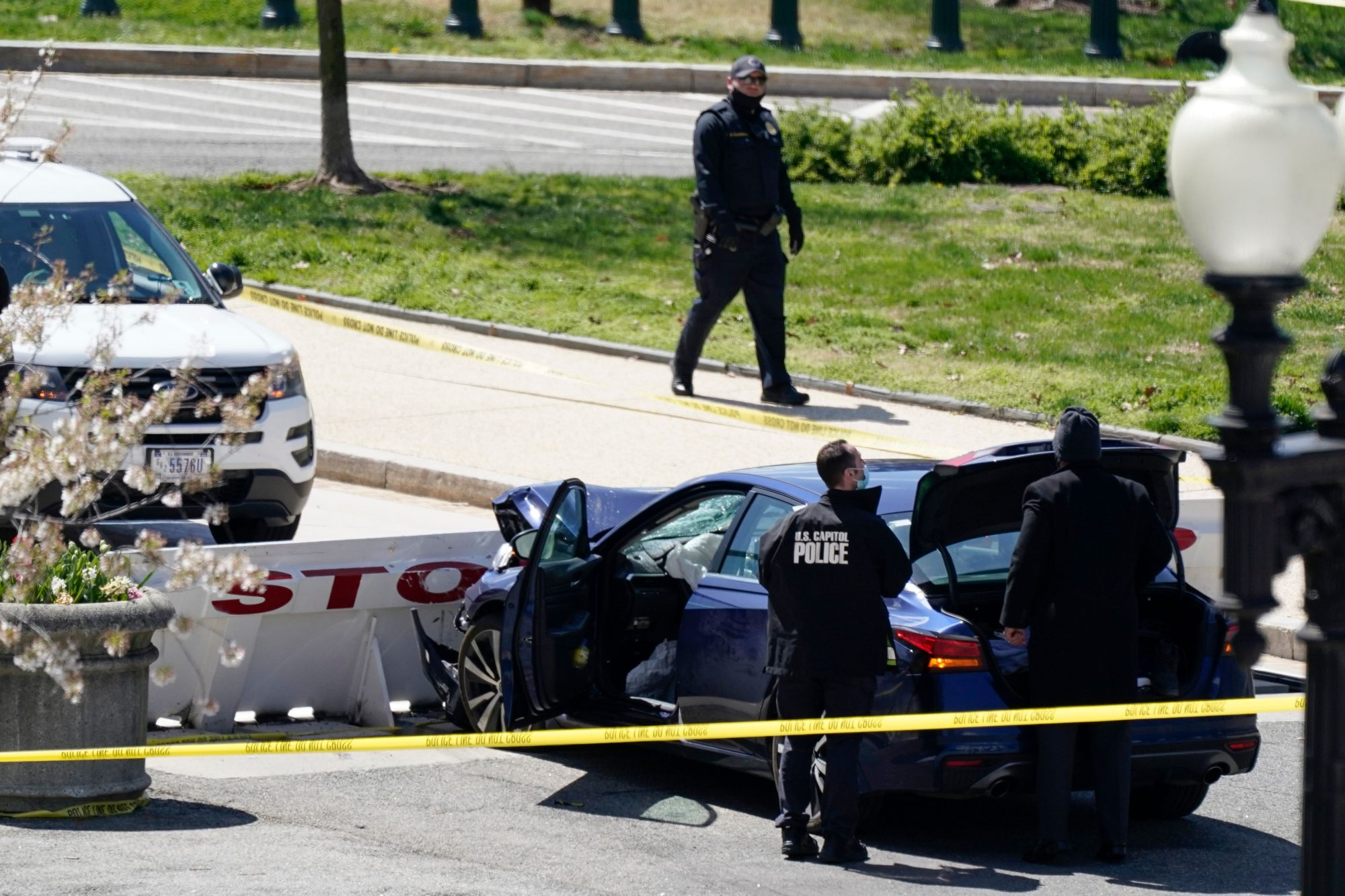 Capitol Police officers stand near a car that crashed into a barrier on Capitol Hill