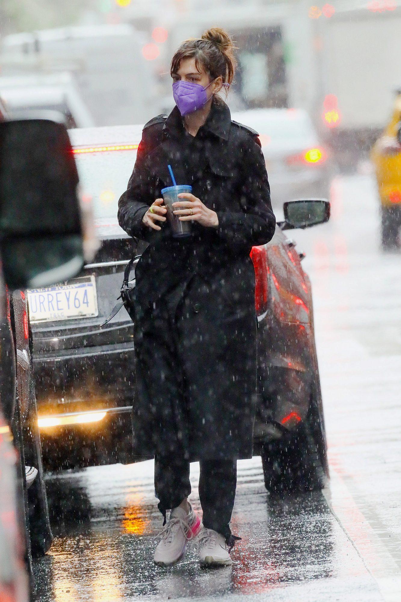 Captamos a la modelo caminando bajo la lluvia con este gabardina negra, pantalón del mismo color y tenis.