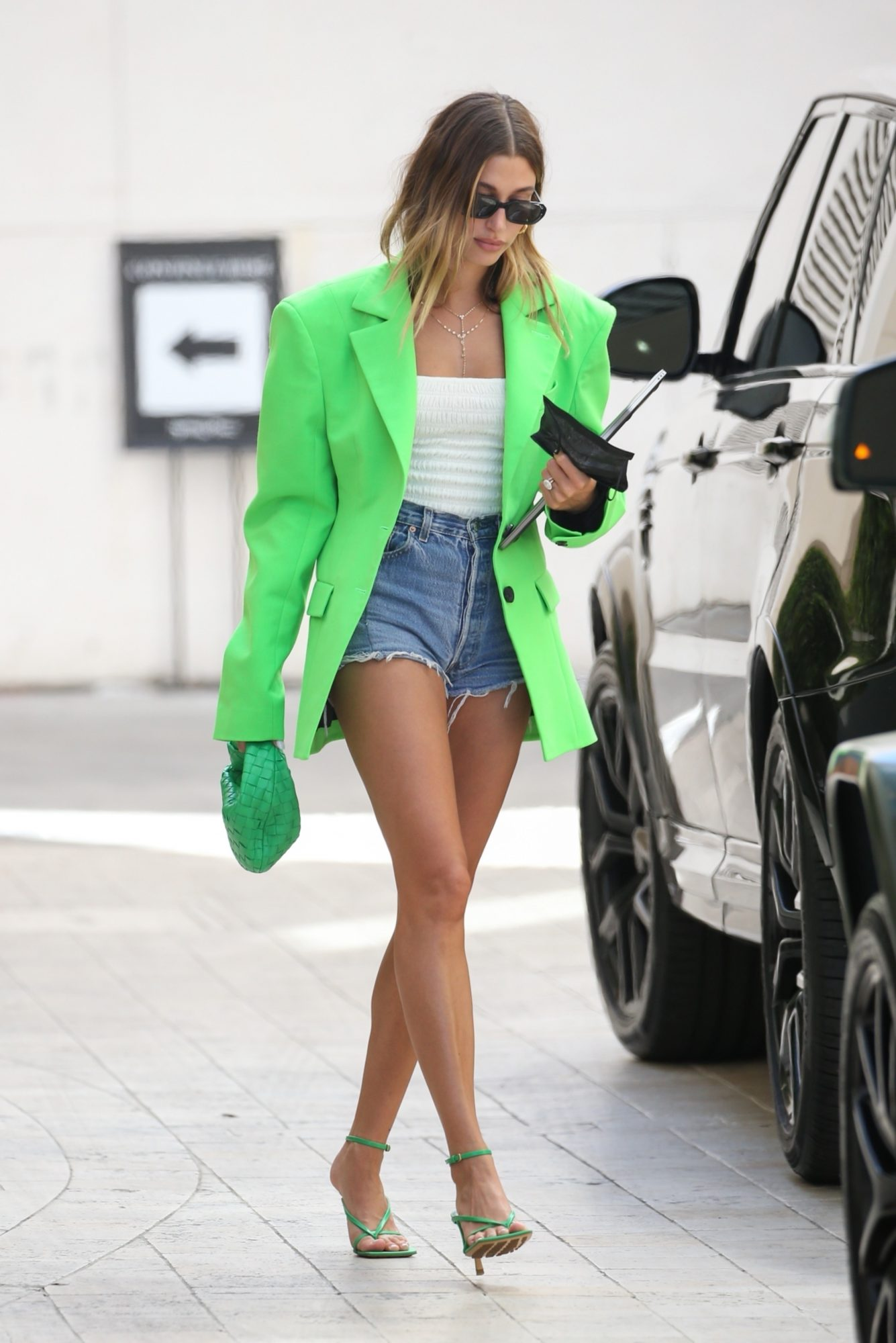 Hailey Bieber, chaqueta oversized verde limon, pantalon corto