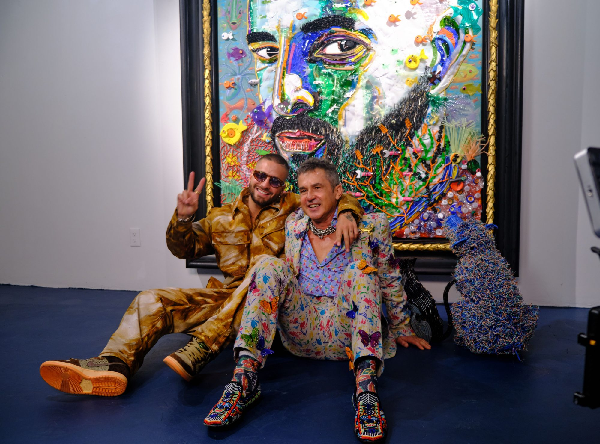 Maluma y el artista Francisco Uribe frente al retrato del cantante colombiano.