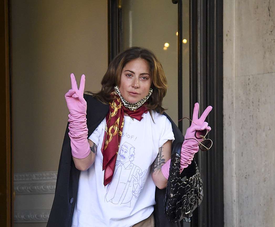 Lady Gaga Looks Emotional as she Dons Pink Gloves to Give Flowers to Fans while leaving her Rome Hotel