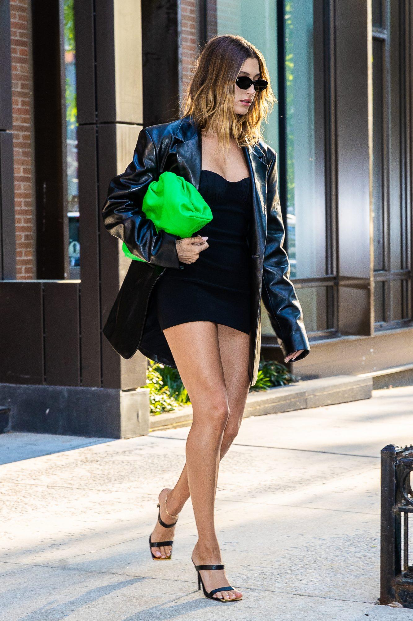Hailey Bieber, minivestido negro, bolso verde neon