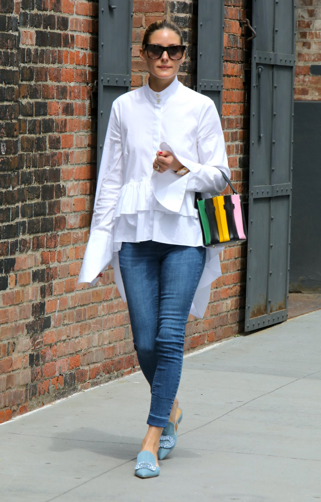 La socialité se paseó por las calles de Nueva York con este look superchic de jeans, camisa blanca con vuelos, zapatos azul. pastel y minibolso a rayas.