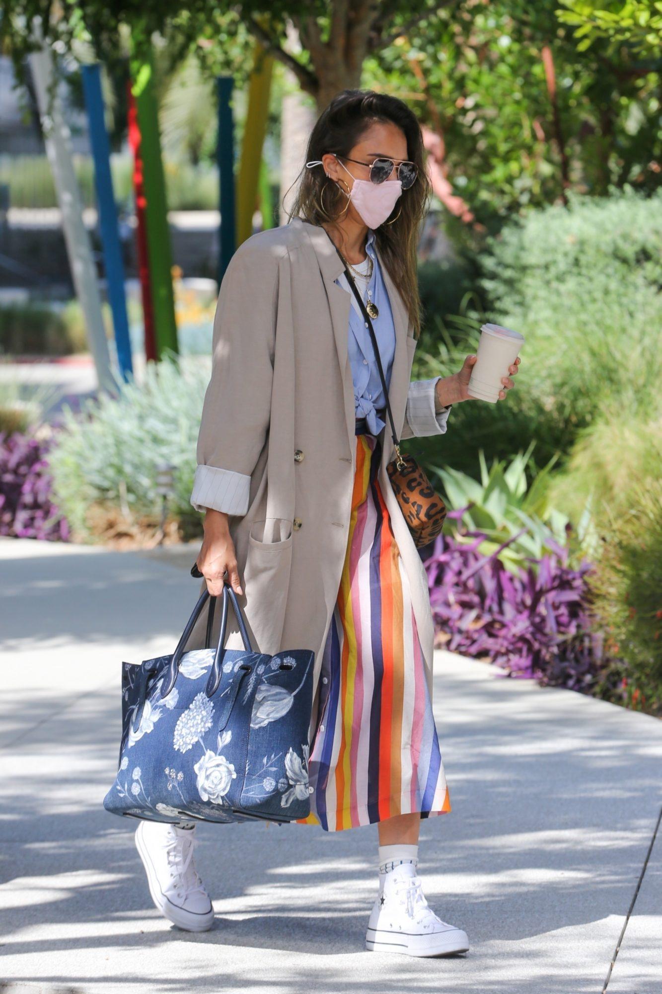Para ir a las oficinas de su compañía, la actriz eligió este look de falda a rayas multicolor, camisa azul, tenis blancos y gabardina caqui.