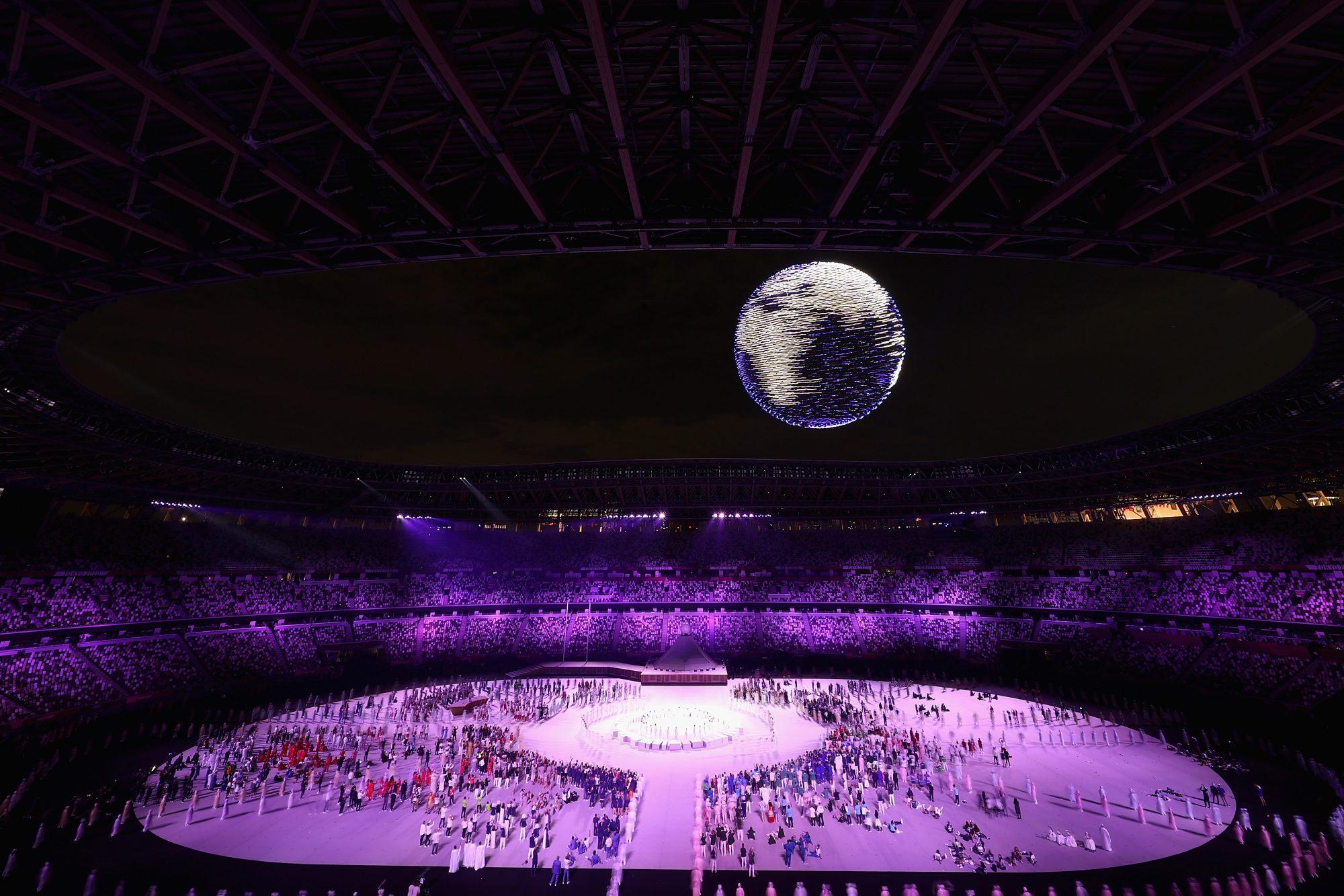 """Por supuesto, la tecnología japonesa no se podía quedar fuera de esta fiesta. Unos 1,800 drones crearon un impresionante globo terráqueo que iluminó el cielo de la ciudad de Tokio, al mismo tiempo que se escuchaba la canción """"Imagine"""" de John Lennon."""