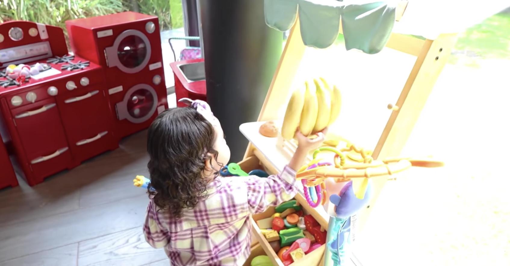 Al igual que su mami, la adorable Kima tiene una cocina súper completa con estufa, lavadora, secadora y ¡hasta una frutería! donde le 'cocina' a sus papis. ¡Qué linda!