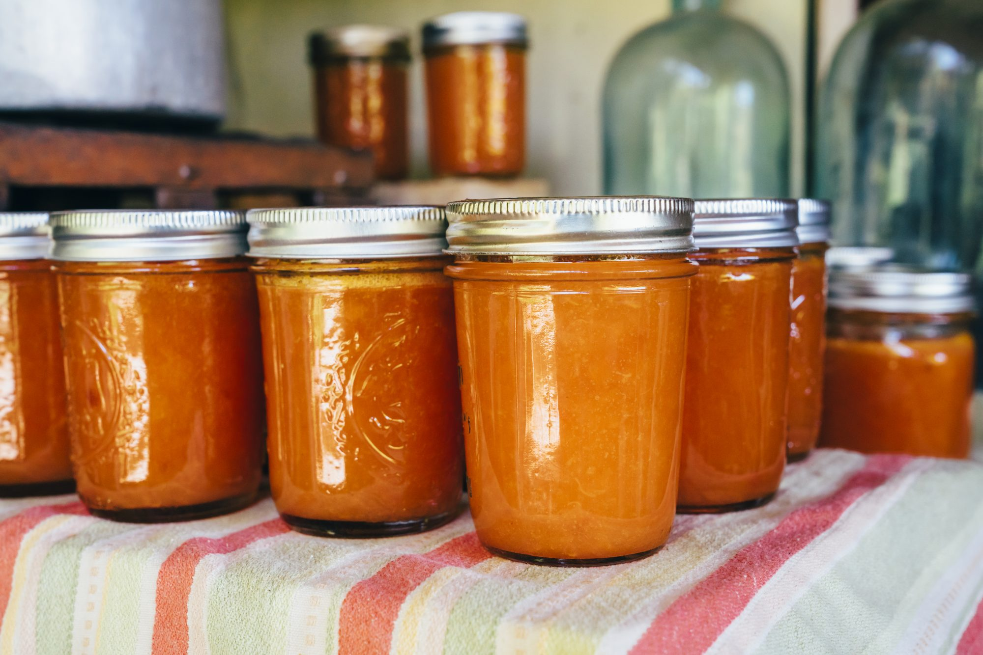 Jars of peach jam on table
