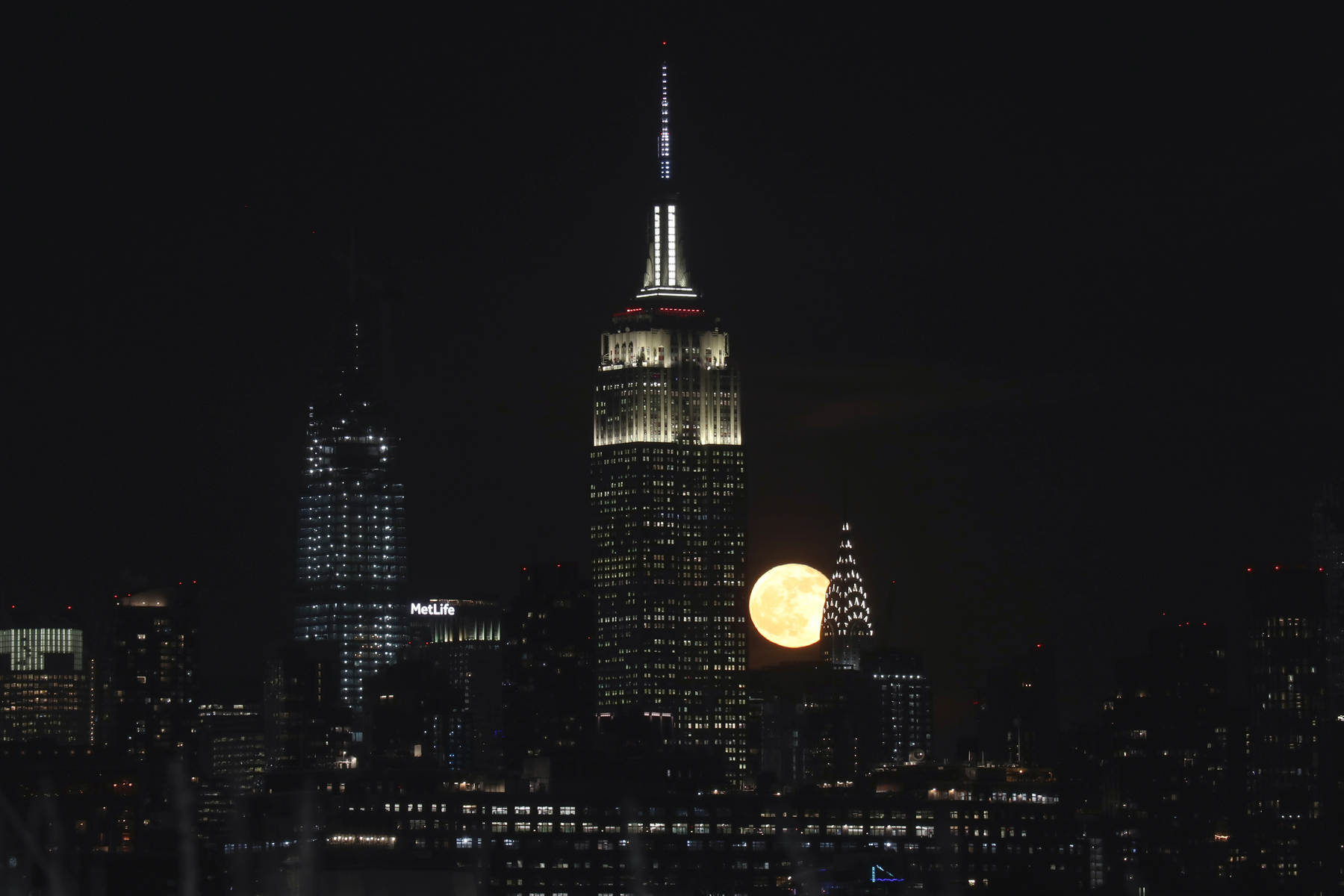 The full Cold Moon rises behind the Empire State Building and Chrysler Building in New York City on December 12, 2019 as seen from Jersey City, New Jersey.
