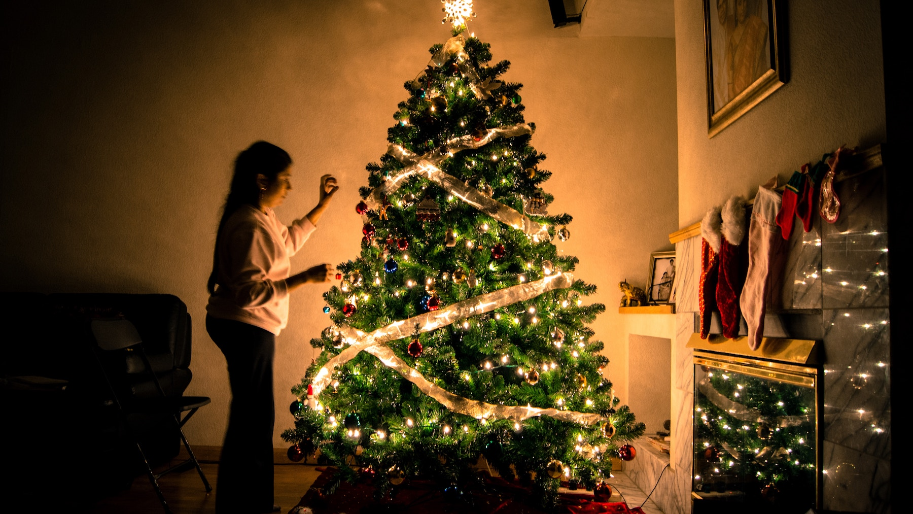 Christmas tree with ribbon and woman decorating