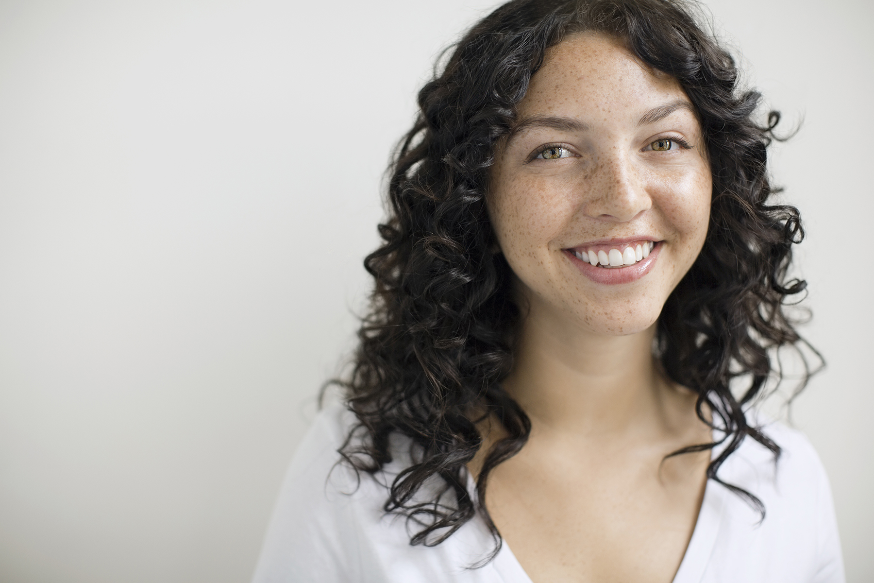 Woman with freckles and dark curly hair