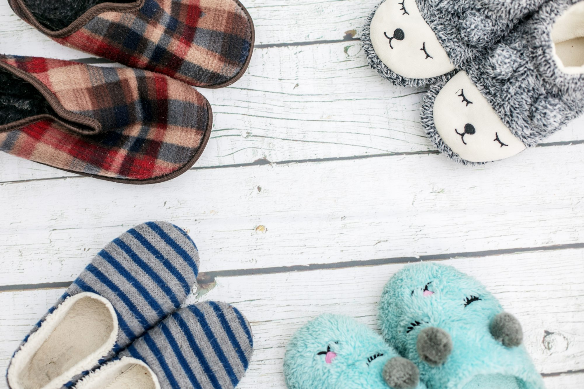 Top view family slippers in white rustic wooden