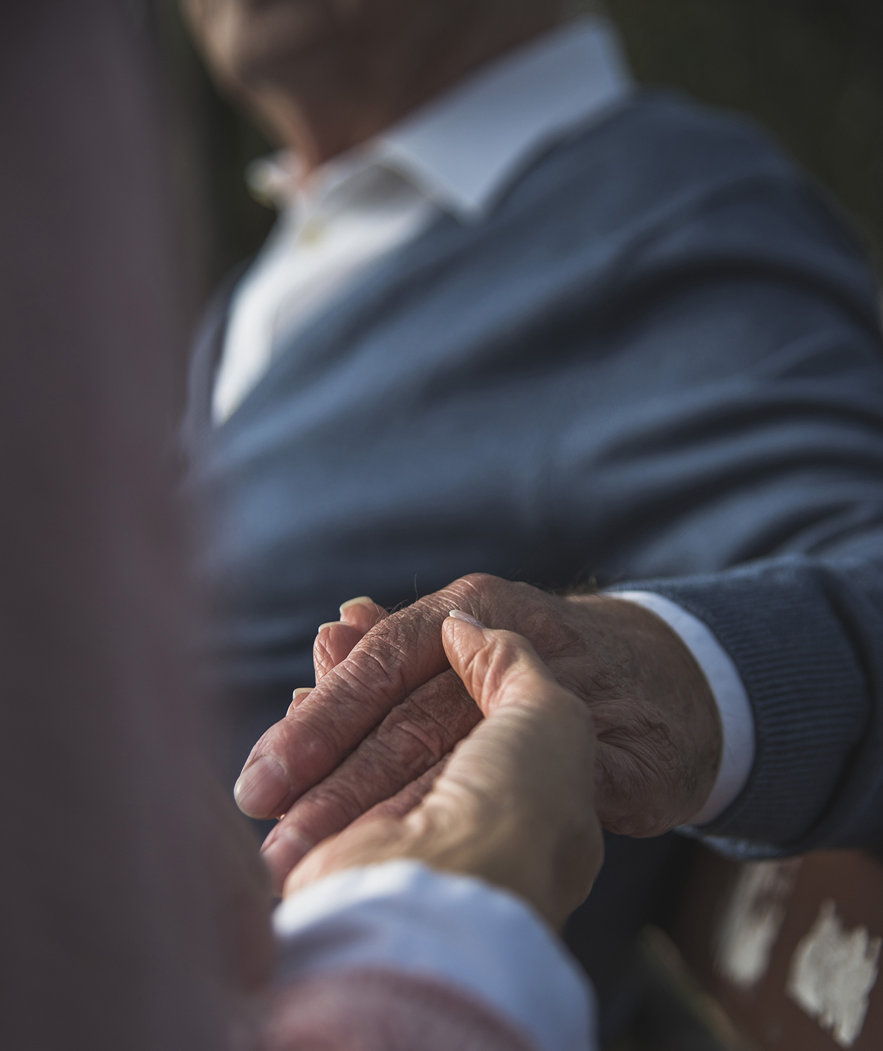 Woman holds elderly father's hand