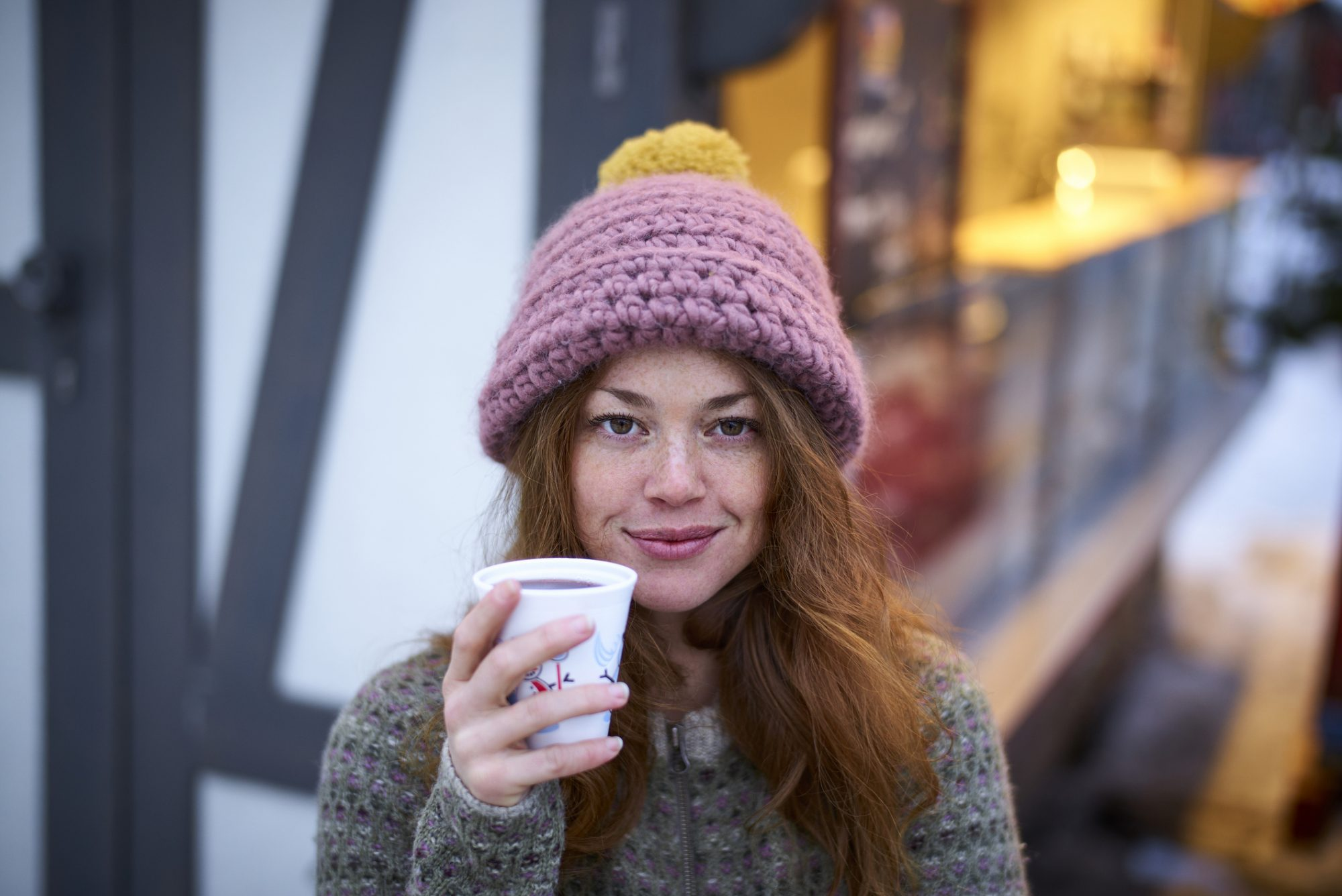 Red hair woman drinking mulled wine