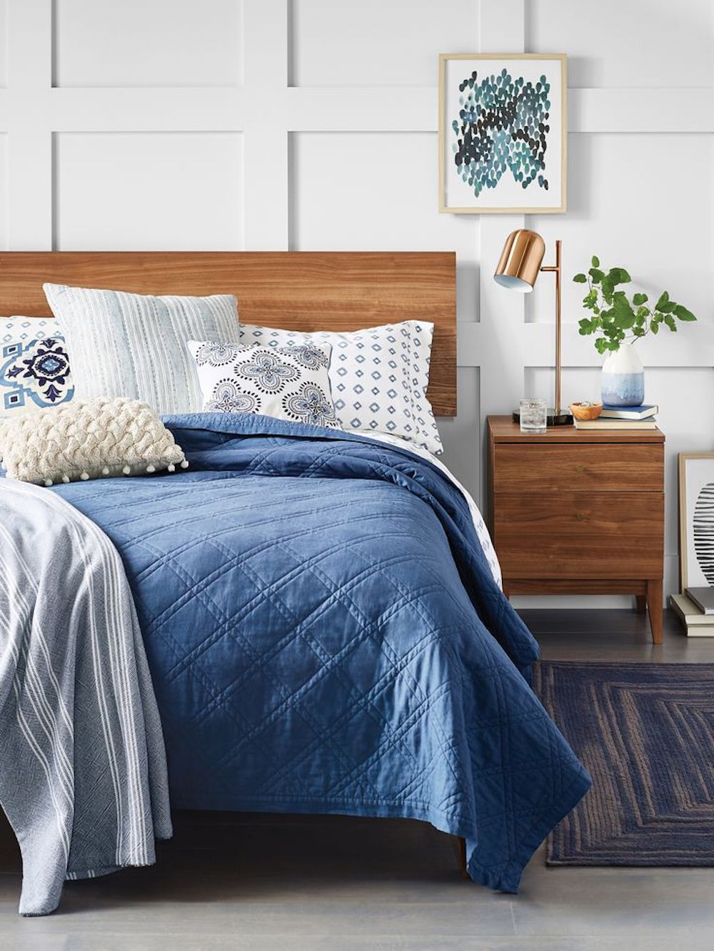 Bed with blue comforter and wooden headboard