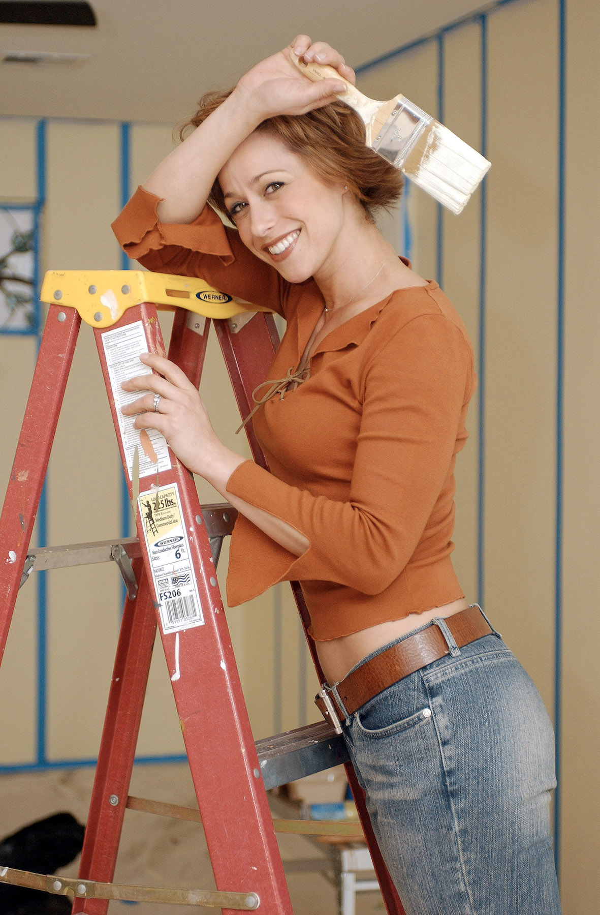 Trading Spaces Paige Davis with paintbrush on ladder
