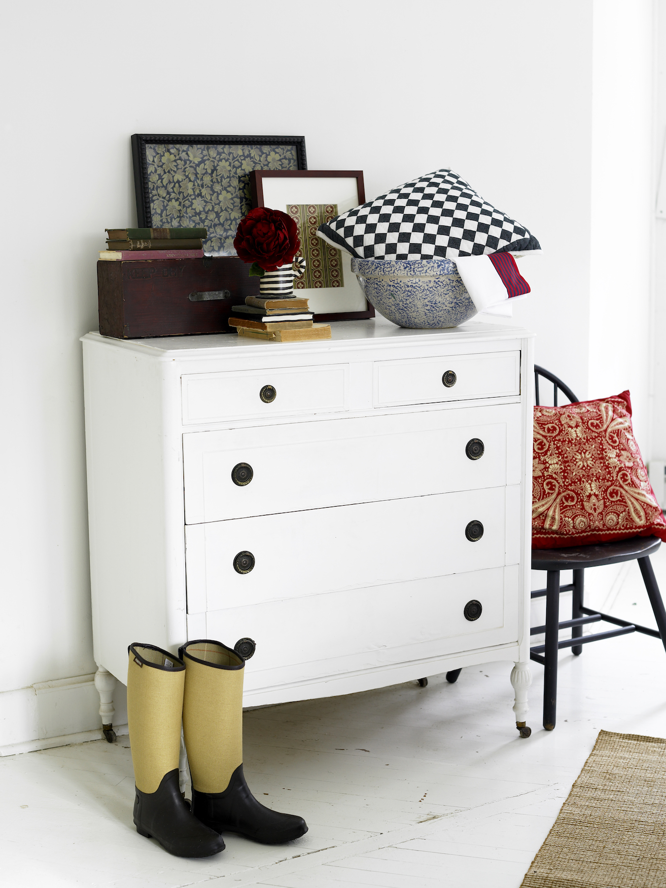 White dresser with boots, pillow, and chair