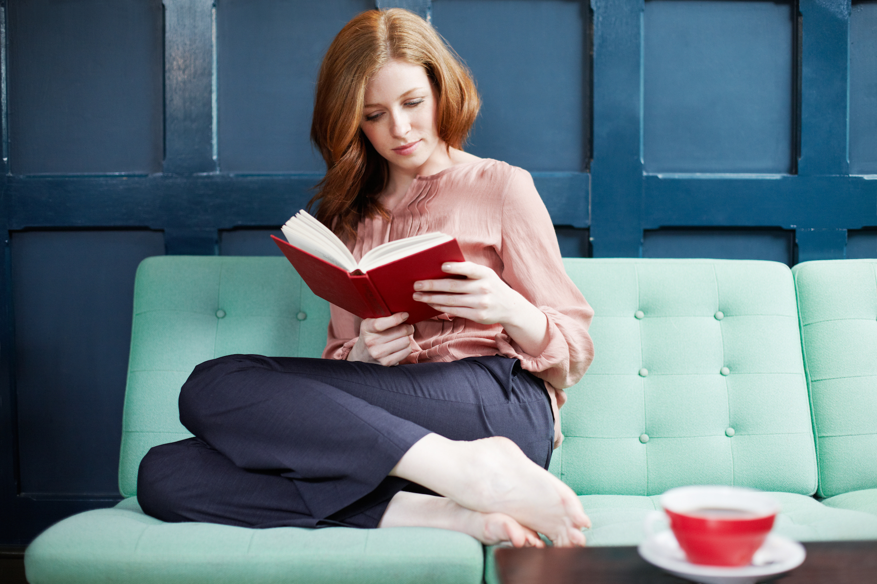 Woman reading book on colorful couch