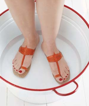 Woman wearing sandals in bucket of water