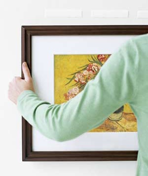 Woman using velcro to hang a picture