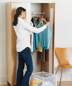 Woman taking clothes out of closet
