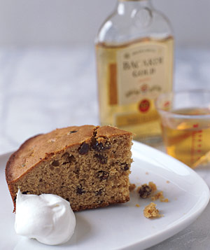 Slice of cake on a plate with rum in background