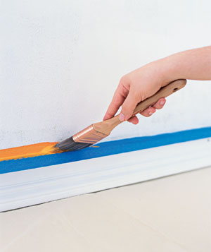 Paint being applied to wall edge with a brush