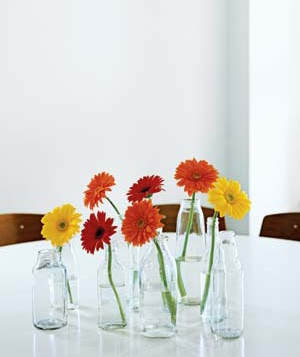 Cluster of milk bottles containing flowers on a table