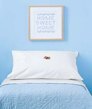 """Home Sweet Home"" embroidery hung above a bed in a blue bedroom"