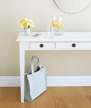 White table with a pitcher of lemon water on it in an entryway